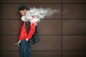Man vaping a modern mod vape vaping device highlighting the technology innovations have benefitted vapers in 2020 including more powerful clearomizers